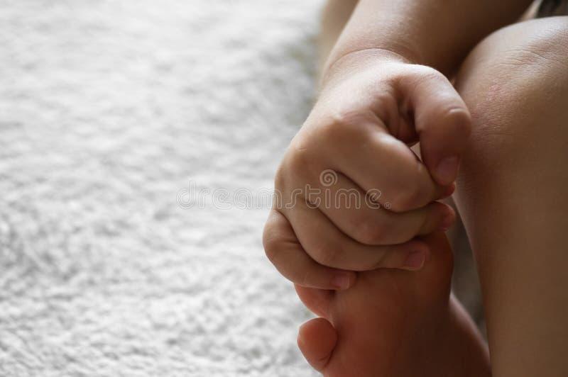Mały dziecko trzyma jego lub jej rękę na woolen białym tle skóra noga Pojęcia dla dzieci Mateczny pomocy pomocy pojęcie obraz stock