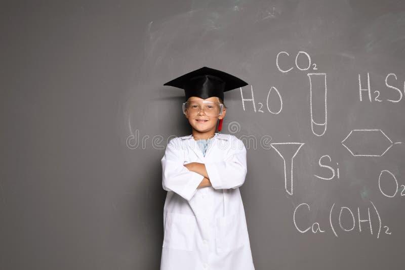 Mały dziecko w wieku szkolnym w laboratorium mundurze z magisterską nakrętką zdjęcia stock