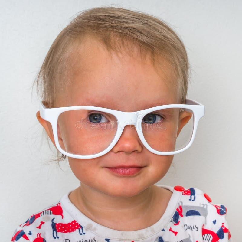 Mały dziecko z eyeglasses odizolowywającymi na bielu zdjęcie royalty free