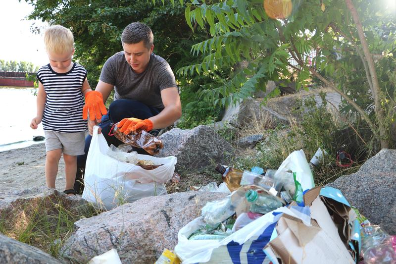 Mały dziecko zbiera grat na plaży Jego tata wskazuje jego palec gdzie rzucać śmieci Rodzice uczą dzieciom czystość obraz royalty free