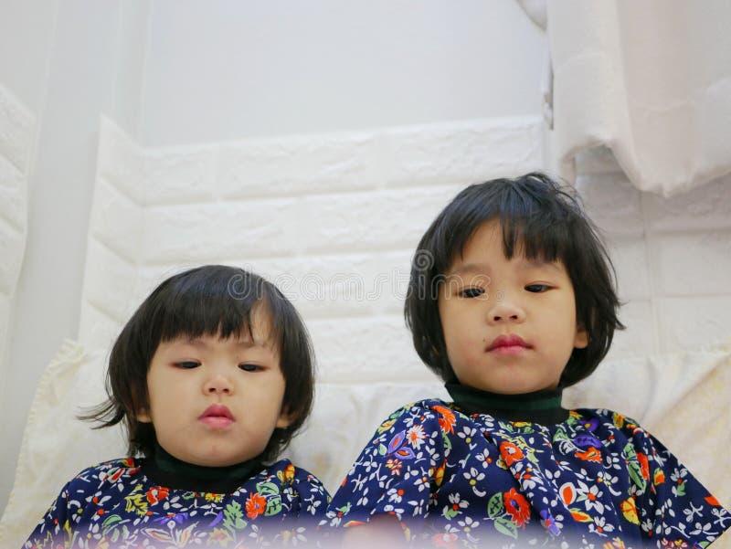 Mały dziewczynek twarzy, siostr, 2 i 3 lat, podczas gdy oglądać/gapi się przy smartphone zdjęcia stock