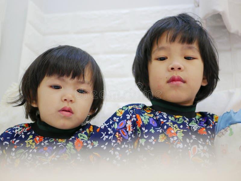 Mały dziewczynek twarzy, siostr, 2 i 3 lat, podczas gdy oglądać/gapi się przy smartphone zdjęcie royalty free