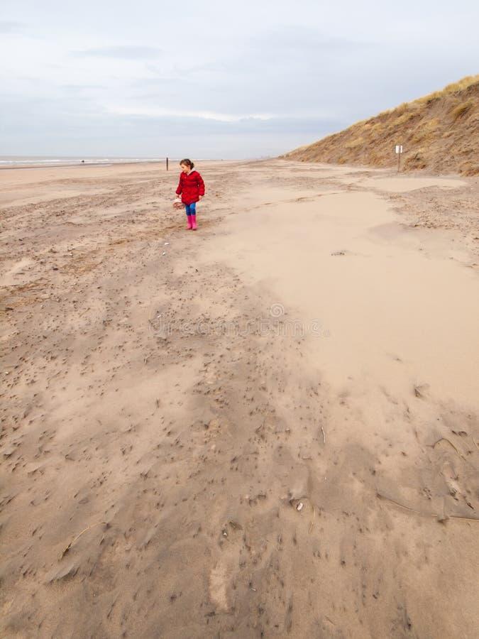 Mały dziewczyny odprowadzenie na plaży w zimie obrazy stock