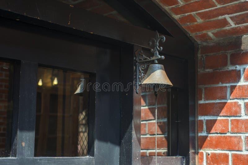 Mały dzwon na starym czerwonym drzwi obraz royalty free