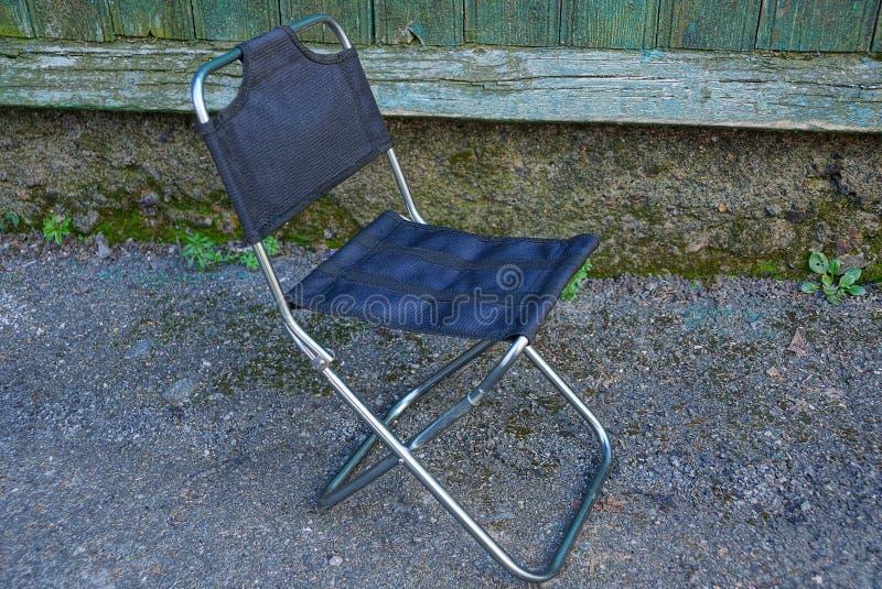 Mały falcowanie metalu krzesło z czarnymi sprawa stojakami na asfalcie przeciw ścianie outside zdjęcie royalty free