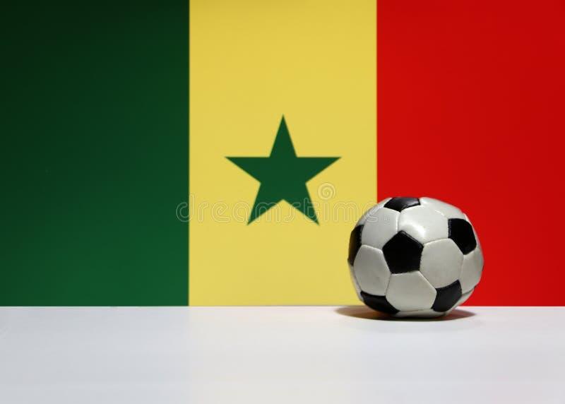 Mały futbol na białej podłoga i Senegalski naród zaznaczamy tło w zieleni, kolorze żółtym i czerwonym kolorze, zdjęcia royalty free