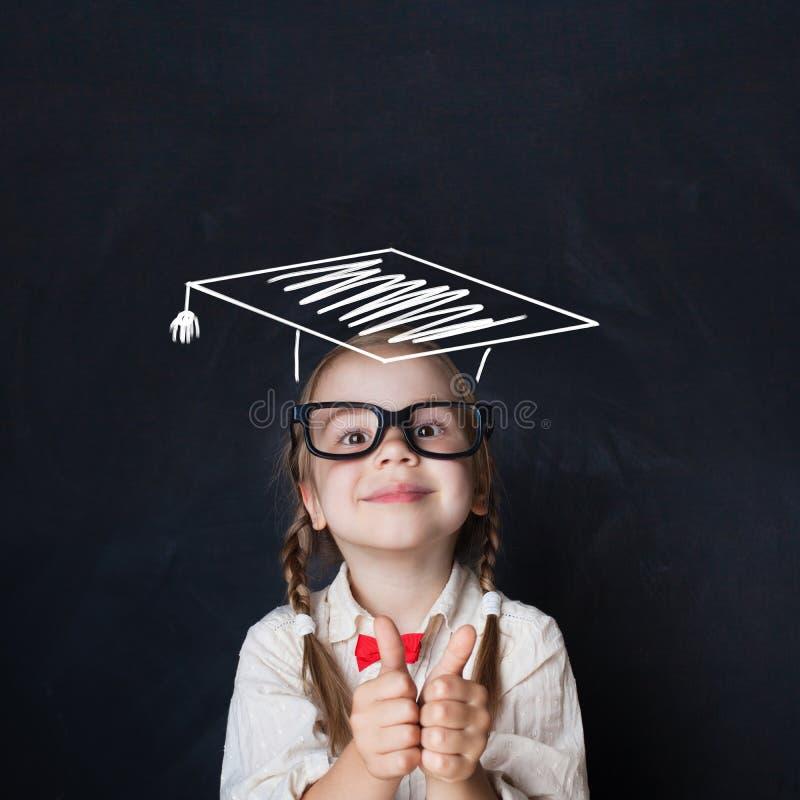 Mały genialny dzieciak w skalowanie kapeluszu z kciukiem up zdjęcie royalty free