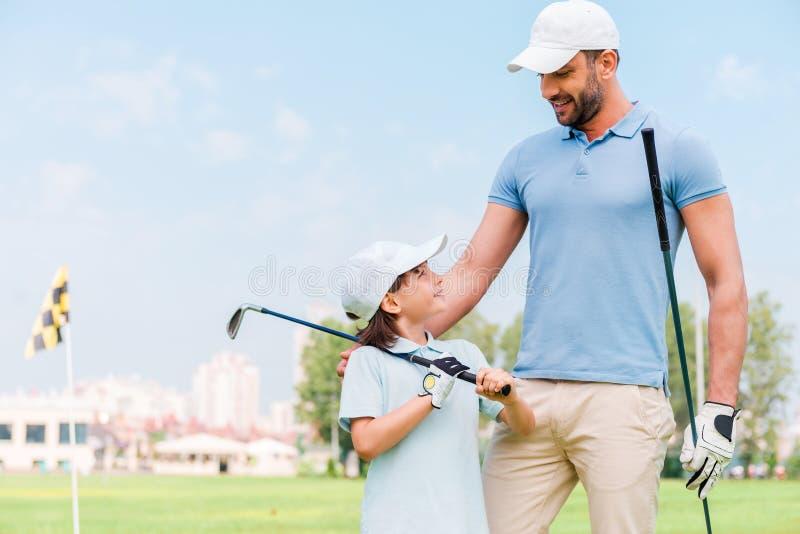 Mały golfista z ojcem zdjęcia stock