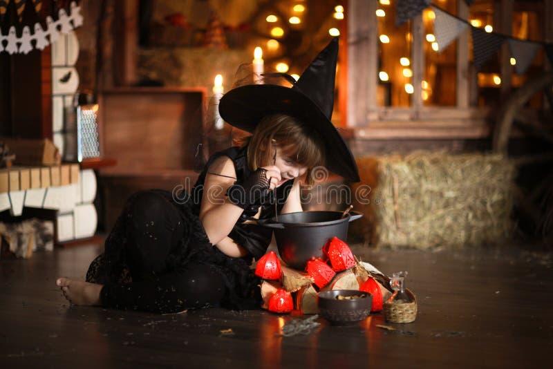 Mały Halloweenowy czarownicy czytanie czaruje nad garnka dzieciństwo h obrazy stock