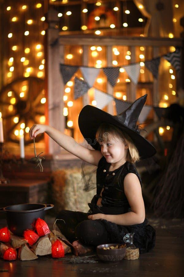 Mały Halloweenowy czarownicy czytanie czaruje nad garnka dzieciństwo h zdjęcia stock