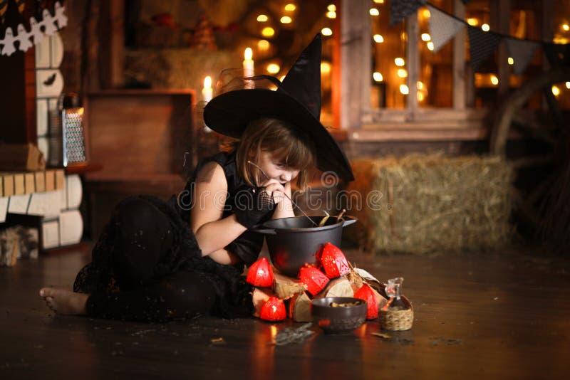 Mały Halloweenowy czarownicy czytanie czaruje nad garnka dzieciństwo h fotografia stock