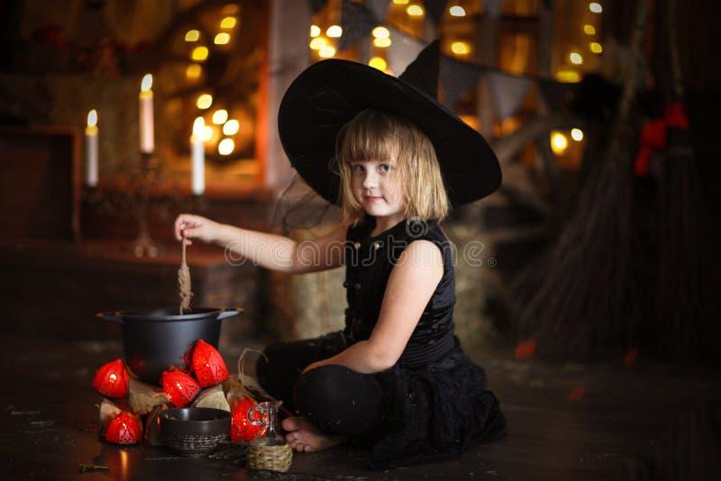 Mały Halloweenowy czarownicy czytanie czaruje nad garnka dzieciństwo h zdjęcie stock
