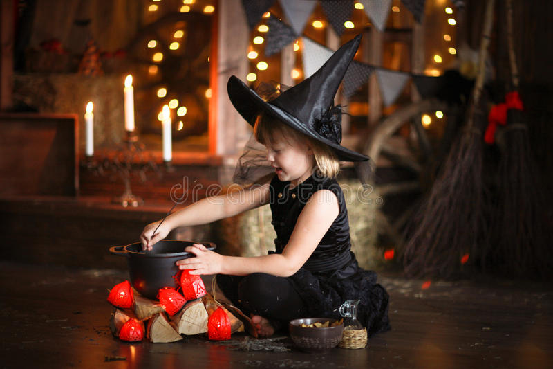 Mały Halloweenowy czarownicy czytanie czaruje nad garnka dzieciństwo h obraz stock