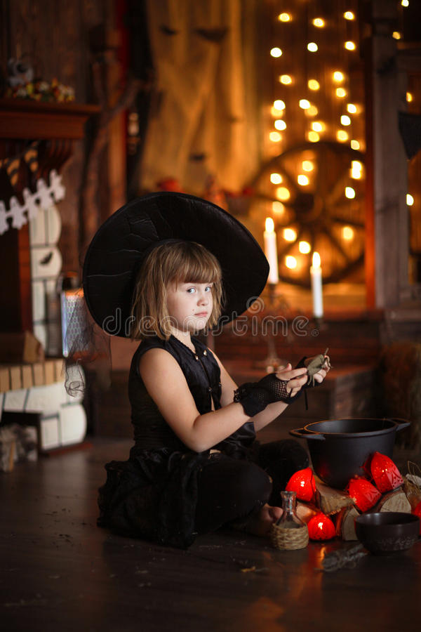 Mały Halloweenowy czarownicy czytanie czaruje nad garnka dzieciństwo h fotografia royalty free