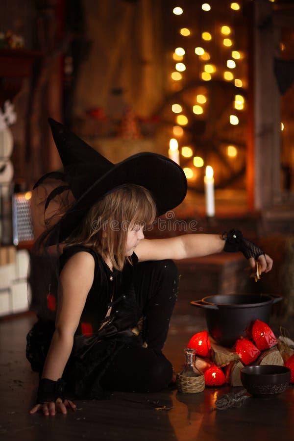 Mały Halloweenowy czarownicy czytanie czaruje nad garnka dzieciństwo h zdjęcia royalty free