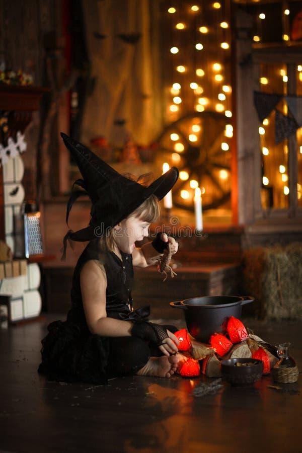 Mały Halloweenowy czarownicy czytanie czaruje nad garnka dzieciństwo h obrazy royalty free