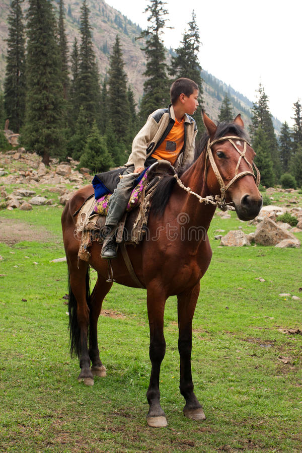 Mały jeźdza obsiadanie na brown koniu w dolinie między górami Środkowy Azja zdjęcie royalty free
