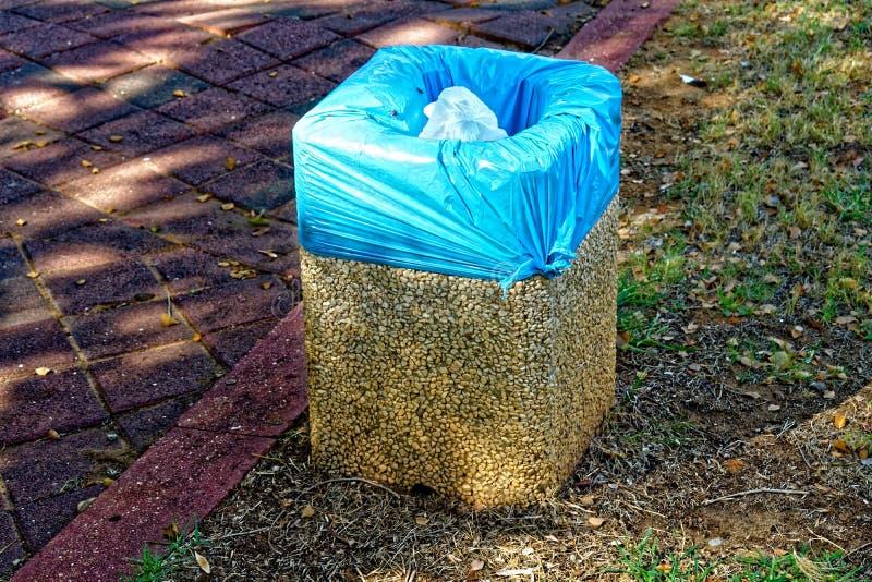 Mały kamienia kubeł na śmieci z błękitnym torba na śmiecie zdjęcie royalty free