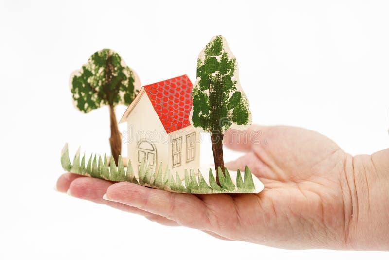 Mały kartonu dom z drzewami jest na palmie twój ręka zdjęcia stock