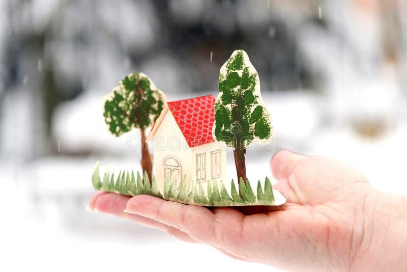 Mały kartonu dom z drzewami jest na palmie twój ręka zdjęcie stock