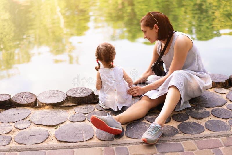 Mały Kaukaski dziewczyny obsiadanie obok jej matki na brzeg sztuczny jezioro w parku Matka z córką na spacerze dalej zdjęcia stock