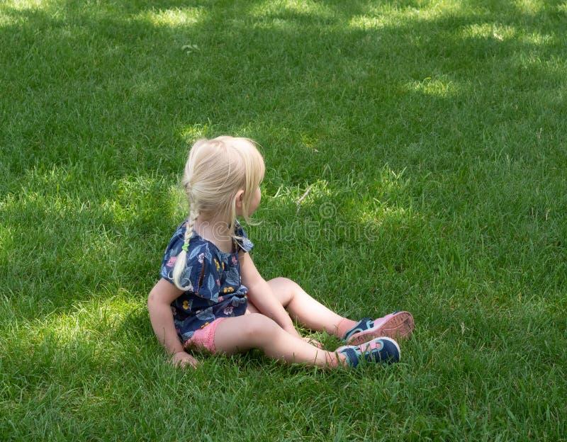 Mały Kaukaski dziewczyny obsiadanie w Zielonej trawie fotografia stock