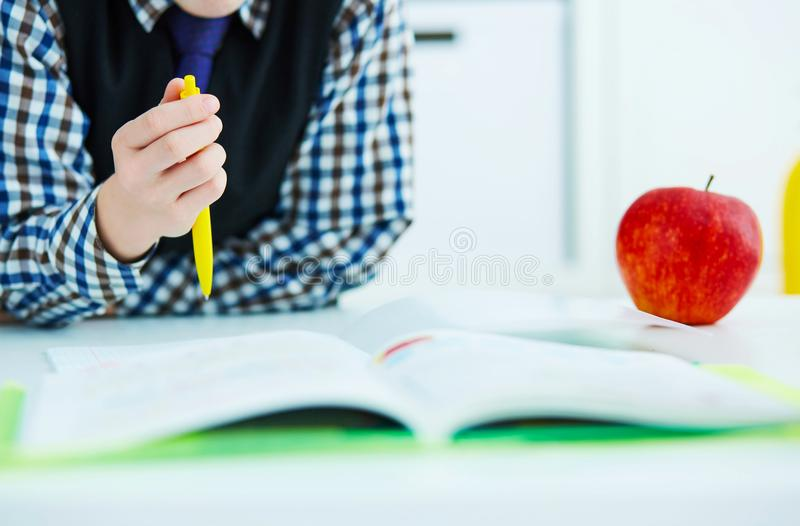 Mały Kaukaski uczniowski writing w notatnika obsiadaniu przy stołem Czerwony jabłko kłama obok stołu Czas dla lunchu fotografia stock