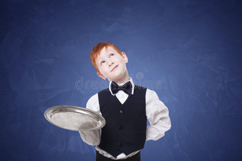 Mały kelner rozważny, marzący z pustą tacą zdjęcia royalty free