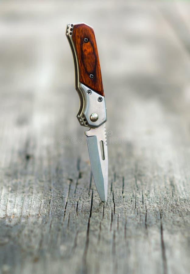 Download Mały Kieszeniowy Nóż Dźgający W Drewnianego Stół Zdjęcie Stock - Obraz złożonej z drewno, nowożytny: 53792598