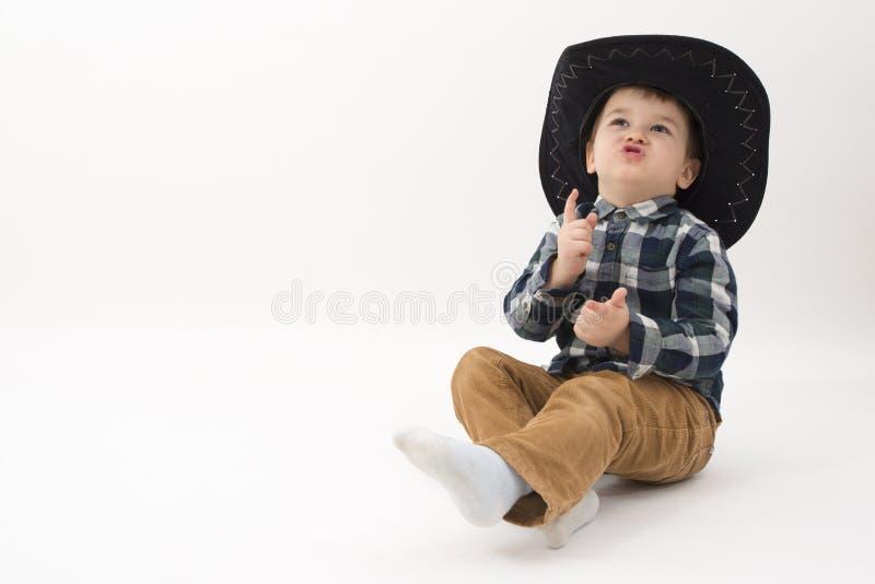 Mały kowboj z czarnym kapeluszem odizolowywającym na bielu fotografia royalty free