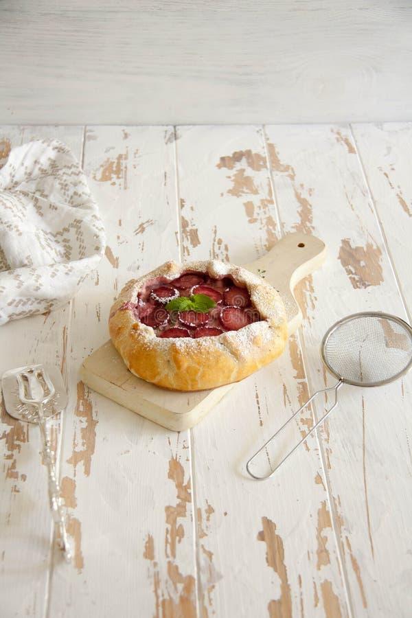 Mały kulebiak z kremowym serem, świeżą truskawką i mennicą, zdjęcia royalty free