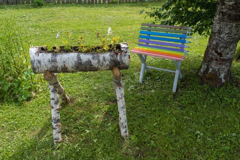Mały kwiatu ogród robić brzoz bele i mała barwiąca ławka obraz royalty free
