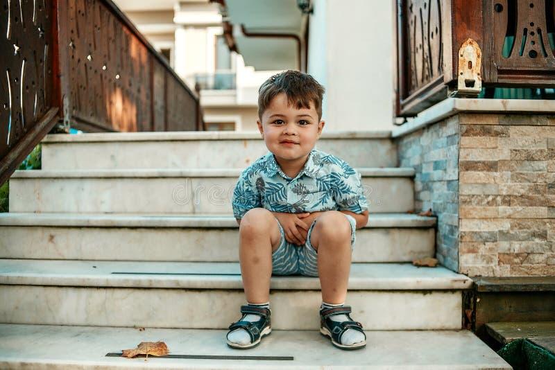 Mały l i bardzo śliczny chłopiec obsiadanie na ono uśmiecha się i schodkach zdjęcia royalty free