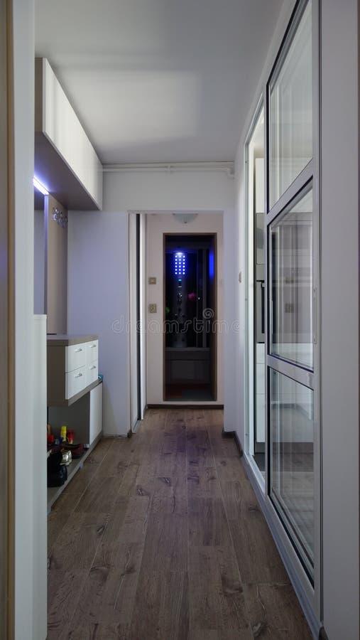 Mały mieszkanie korytarz, wąski wejście z dowodzonymi światłami i duży szklany drzwi oddziela kuchnię, Dowodzeni łazienki błękita obraz royalty free