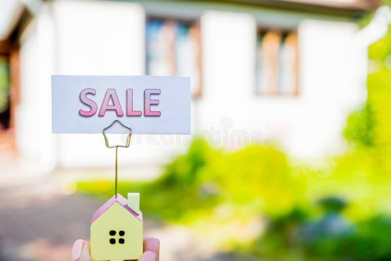 Mały model dom i sprzedaży deska oszczędzanie pieniądze dla mieszkaniowego i przechodzić na emeryturę pojęcia Nieruchomość, oszcz zdjęcia stock