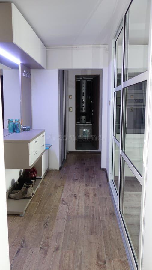 Mały modernistyczny mieszkanie korytarz iluminujący dowodzonymi światłami, duży lustro, duży szklany drzwi oddziela kuchnię obrazy royalty free