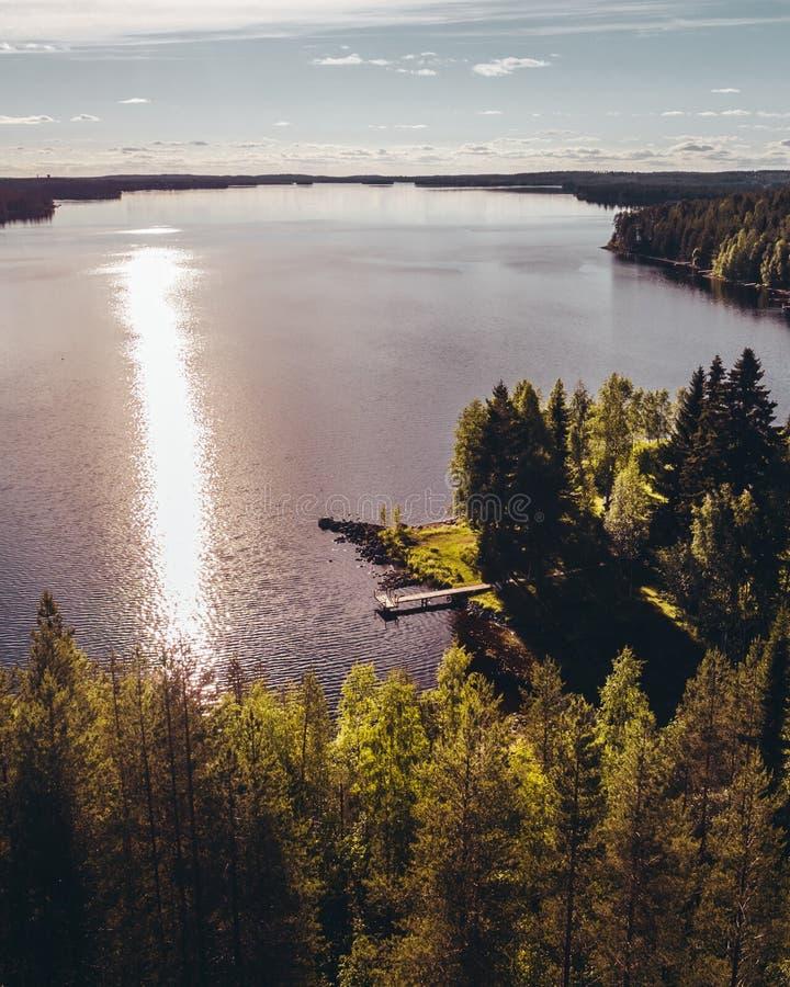 Mały molo przy brzeg duży jezioro na wieczór z słońcem odbija w wodzie obraz royalty free