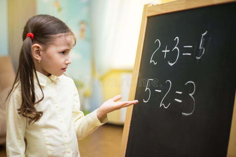 Mały nauczyciel Piękna młoda dziewczyna uczy w domu na blac fotografia stock