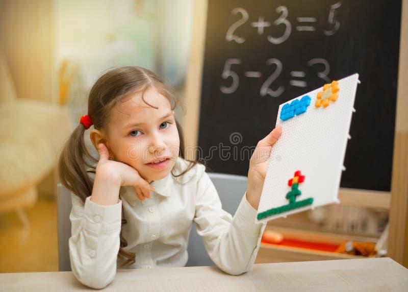 Mały nauczyciel Piękna młoda dziewczyna uczy w domu na blac zdjęcia royalty free