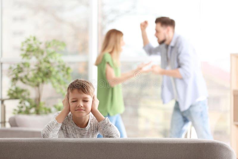 Mały nieszczęśliwy chłopiec obsiadanie na kanapie podczas gdy rodziców dyskutować obraz royalty free
