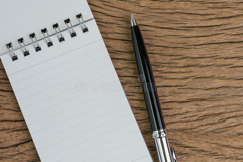 Mały papierowy notepad z pustą stroną, pióro na drewnianym stole używać jako spotkanie notatka, pisać wiadomości lub zadanie liśc obrazy stock