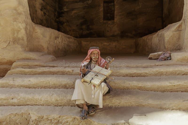 Mały Petra, Jordanowski †'Czerwiec 20, 2017: Stary Beduiński mężczyzna lub Arabski mężczyzna w tradycyjnym stroju, bawić się je zdjęcia royalty free