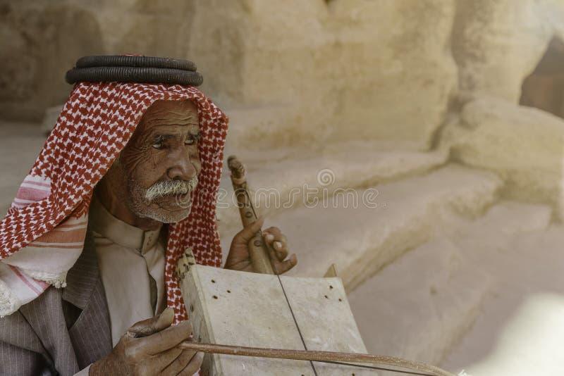 Mały Petra, Jordanowski †'Czerwiec 20, 2017: Stary Beduiński mężczyzna lub Arabski mężczyzna w tradycyjnym stroju, bawić się je zdjęcie royalty free