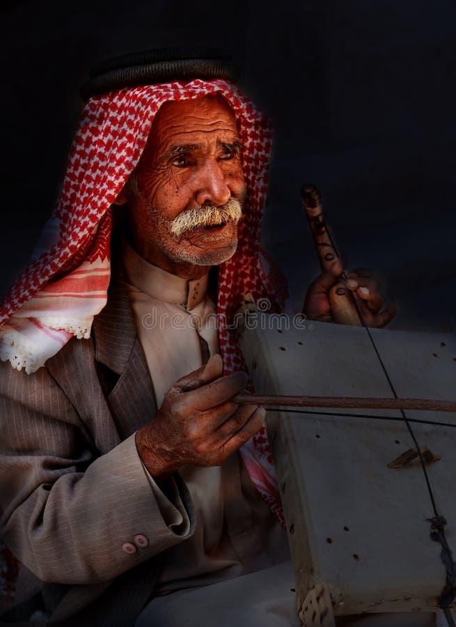 Mały Petra, Jordanowski Czerwiec 20, 2017: Stary Beduiński mężczyzna lub Arabski mężczyzna w tradycyjnym stroju, bawić się je zdjęcie stock