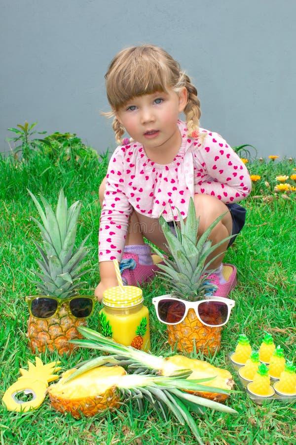 Mały piękny dziewczyny obsiadanie w ogródzie Pinkin z anasas outdoors obrazy stock