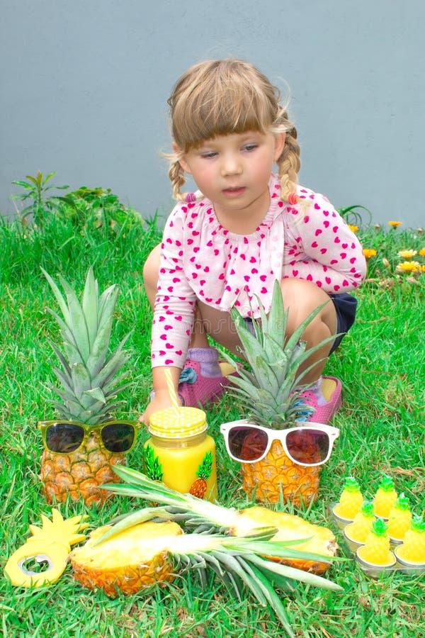 Mały piękny dziewczyny obsiadanie w ogródzie Pinkin z anasas outdoors obrazy royalty free