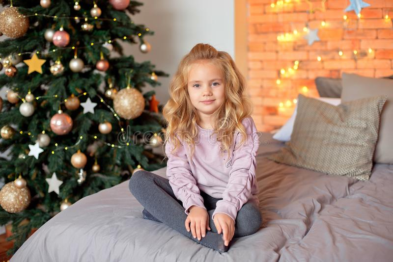 Mały piękny kędzierzawy blondynki dziewczyny obsiadanie na łóżku i ono uśmiecha się na tle choinka obraz royalty free