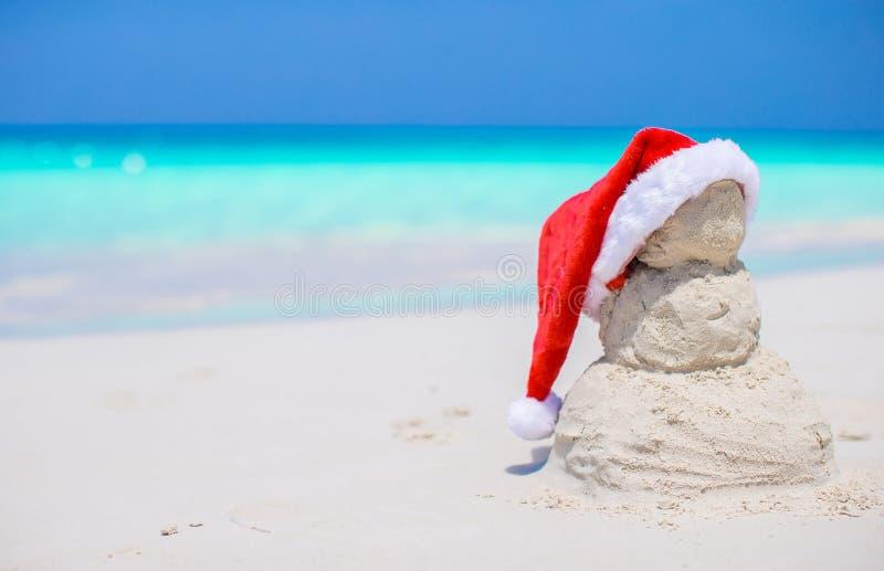 Mały piaskowaty bałwan z czerwonym Santa kapeluszem na bielu zdjęcie royalty free