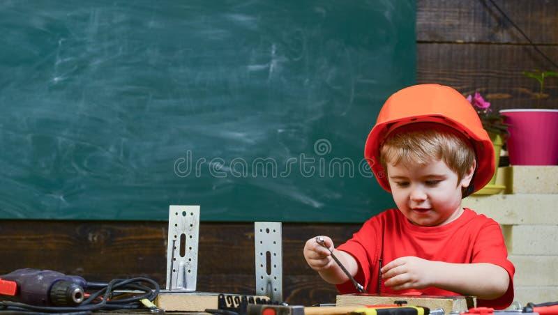 Mały pomagiera pojęcie Dziecko marzy o przyszłościowej karierze w architekturze lub budować Dzieciak chłopiec w pomarańczowym cię zdjęcie stock