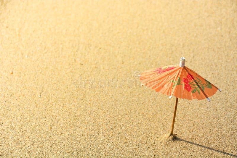 Mały pomarańczowy koktajlu papieru parasol na plażowym piasku z światłem słonecznym na wieczór obraz stock